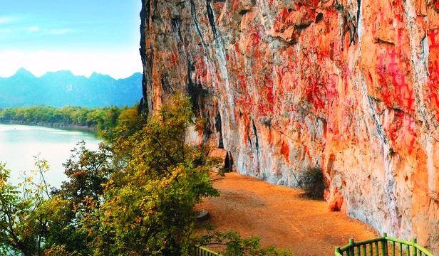 坐船沿明江进去,两岸风景如画。岩画是指分布于崇左市左江两岸、由壮族先民于春秋至战国时期绘制于悬崖峭壁之上的岩画,历经西汉、东汉不断充实,至今已有18002500年的历史。花山岩画绵延数百里,数量多达83处,178个点,280组图像。其中宁明明江花山岩画是目前发现的岩画中面积最大、图像最多、保存最为完好的一处岩画,画面宽170余米,高40余米,面积约8000多平方米,1988年已公布为全国重点文物保护单位。一位前来考察的英国岩画专家认为,花山岩画是世界上总体规模最大的岩画。2016年,花山岩画将作为中国唯一